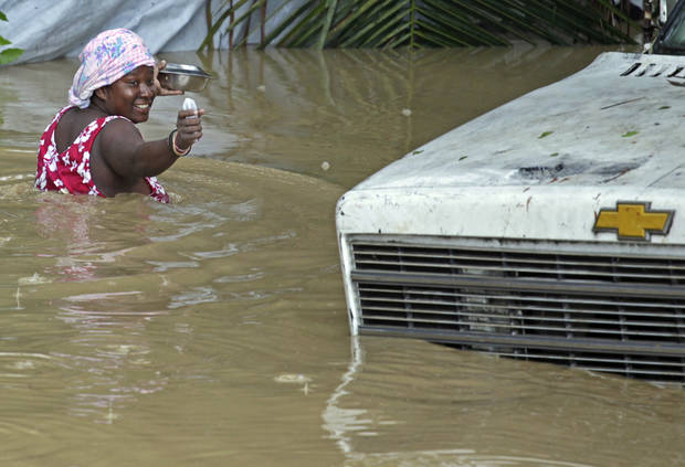 A resident of Leogane, Haiti makes her way to her home as the water level continues to rise Friday, Oct. 26, 2012. Residents of Leogane have had five consecutive days of rain in the aftermath of Hurricane Sandy, which caused serious flooding and claimed at least 26 lives in the impoverished country. (AP Photo/The Miami Herald, Carl Juste) MAGS OUT