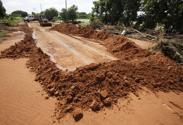 Edmond city workers scoop hundreds of tons of sand off of Danforth Rd. just west of Douglas in Edmond, OK, after yesterday's torential rains deposited the sand more than three feet deep across the road, Tuesday, June 15, 2010. By Paul Hellstern, The Oklahoman