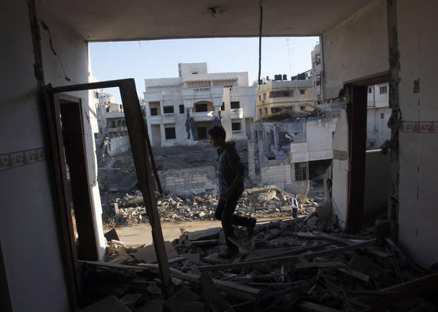 A Palestinian youth walks through a damaged apartment hit in an Israeli strike, in Gaza City ,Thursday, Nov. 15, 2012. Israeli aircraft, tanks and naval gunboats pounded the Hamas-ruled Gaza Strip and rocket salvoes thudded into southern Israel, as residents on both sides of the frontier holed up at home in anticipation of heavy fighting on the second day of Israel's offensive against Islamic militants. (AP Photo/Hatem Moussa)