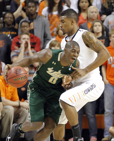 Oklahoma State 's Le'Bryan Nash (2) fouls South Florida Bulls' Martino Brock (0) during the college basketball game between Oklahoma State University (OSU) and the University of South Florida (USF) on Wednesday , Dec. 5, 2012, in Stillwater, Okla.   Photo by Chris Landsberger, The Oklahoman
