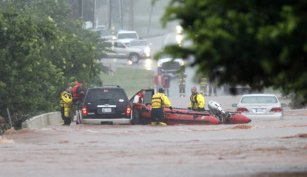 Oklahoma City firefighters rescue two stranded motorists from a bridge near Hefner Road and Sooner in Oklahoma City, Oklahoma June 14 , 2010. Photo by Steve Gooch, The Oklahoman