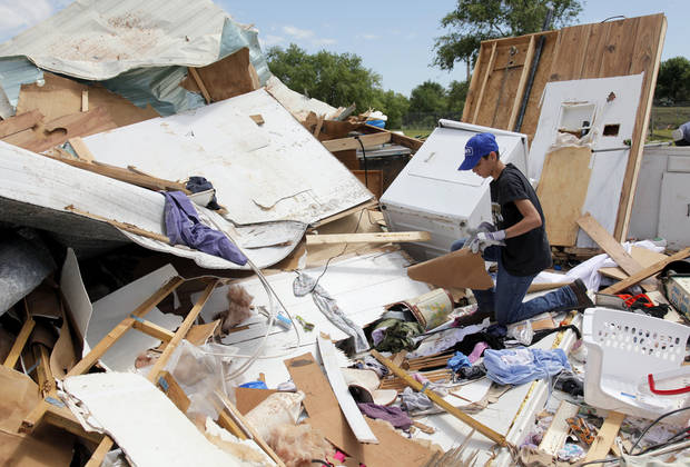 Braiden Key, 13, searches through what is left of the home of his aunt and uncle, Christal Key and Brian Key, at the Hide-A-Way Mobile Home Park in Woodward, Okla., Monday, April 16, 2012.  A tornado struck the town early Sunday morning. Photo by Nate Billings, The Oklahoman
