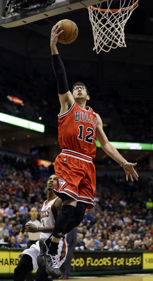 Chicago Bulls' Kirk Hinrich (12) puts up a shot as Milwaukee Bucks' Brandon Jennings, left, looks on during the first half of an NBA basketball game Wednesday, Jan. 30, 2013, in Milwaukee. (AP Photo/Jeffrey Phelps)