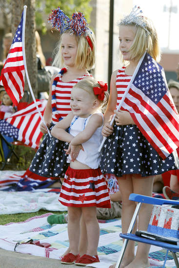 Sisters Harper Sage, left, 8, Crosby,2, and Stella, 8, enjoy the annual LibertyFest Fourth of July Parade in downtown Edmond, OK, Thursday, July 4, 2013,  Photo by Paul Hellstern, The Oklahoman