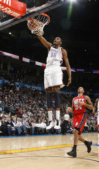 Oklahoma CIty's Kevin Durant dunks the ball in front of New Jersey's Devin Harris during the NBA basketball game between the Oklahoma City Thunder and the New Jersey Nets at the Oklahoma City Arena, Wednesday, Dec. 29, 2010.  Photo by Bryan Terry, The Oklahoman
