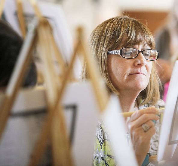 Carla Hawkins works on a piece of art at the Corkscrews and Canvas painting party Thursday at the Santa Fe Depot in Norman. PHOTOS BY NATE BILLINGS, THE OKLAHOMAN