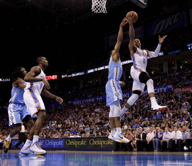 Oklahoma City's Russell Westbrook (0) goes past Denver's Andre Iguodala (9) during an NBA basketball game between the Oklahoma City Thunder and the Denver Nuggets at Chesapeake Energy Arena in Oklahoma City, Tuesday, March 19, 2013. Denver won 114-104. Photo by Bryan Terry, The Oklahoman