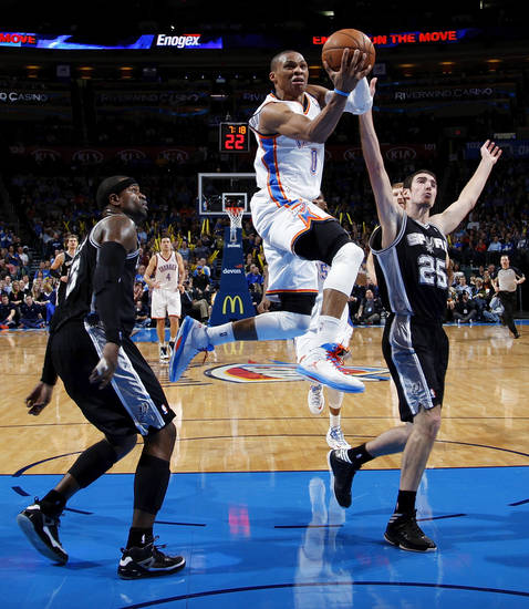 Oklahoma City's Russell Westbrook (0) moves to the hoop between San Antonio's Stephen Jackson (3) and Nando de Colo (25) during an NBA basketball game between the Oklahoma City Thunder and the San Antonio Spurs in Oklahoma City Monday, Dec. 17, 2012. Oklahoma City won, 107-93. Photo by Nate Billings, The Oklahoman