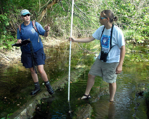 Blue Thumb trainer Jean Lemmon shows Shawnee High School teacher Valerie Bradshaw how to measure water in Delaware Creek.