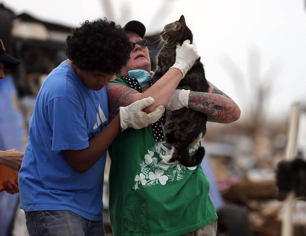 Kristy Parrish is helped of a rubble pile by Said Gudino after volunteers found her cat Hudson Kit-ten in her destroyed home in Moore, Okla., Friday, May, 24, 2013. Photo by Sarah Phipps, The Oklahoman