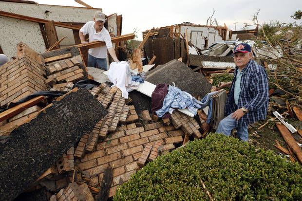 Curt Adams, left, hands his father Jack Adams clothes from inside his tornado damaged home near SW 149th and Western on Monday, May 20, 2013  in Moore, Okla. Photo by Steve Sisney, The Oklahoman