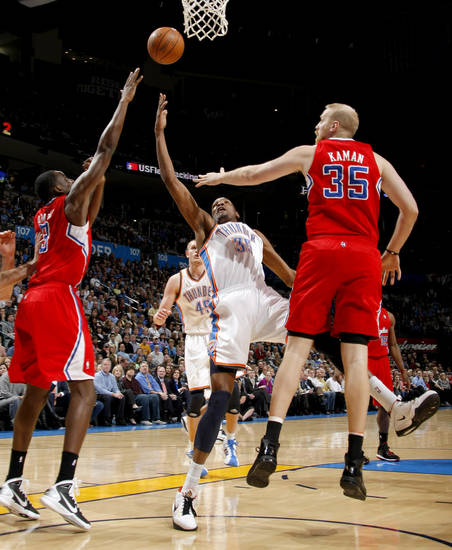 Oklahoma City's Kevin Durant (35) goes between Los Angeles' Al-Farouq Aminu (3) and Chris Kaman (35) during the NBA basketball game between the Oklahoma City Thunder and the Los Angeles Clippers at the Oklahoma CIty Arena, Tuesday, Feb. 22, 2011.  Photo by Bryan Terry, The Oklahoman