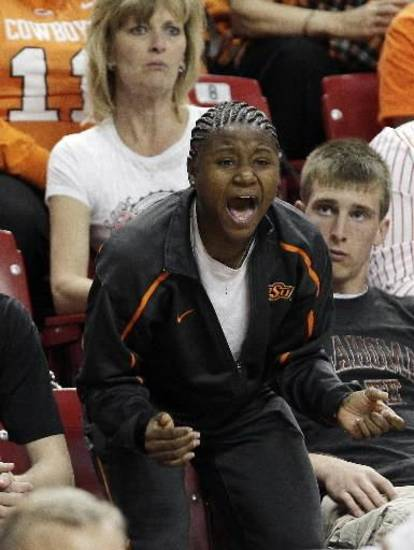 Serving a one-game tournament suspension, Oklahoma State's  Andrea  Riley cheers on her teammates from the stands as they play Chattanooga during the first half of an NCAA college first-round basketball game in Tempe, Ariz., Saturday, March 20, 2010. (AP Photo/Ross D. Franklin)