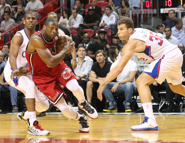 Miami Heat Dwyane Wade drives against  Los Angeles Clippers Chris Paul,left, and Blake Griffin during the first quarter  of  an NBA game at the AmericanAirlines Arena in Miami on Friday, Feb. 8, 2013. (AP Photo/El Nuevo Herald, David Santiago)