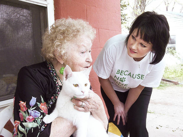 Bertie Allison holds her cat Snowball at her home in southwest Oklahoma City and talks to Pet Food Pantry volunteer Tami Golden on Saturday. The 71-year-old depends on the pantry to help her care for her animals.  Photos by Susan Wright, For The Oklahoman
