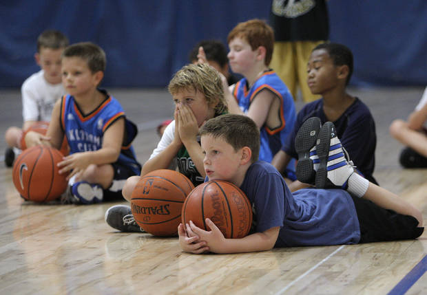 Participants take a break to listen to instruction during the Blake Griffin basketball camp at the Santa Fe Family Life Center in Oklahoma City Thursday, Aug. 4, 2011.  Photo by Garett Fisbeck, The Oklahoman