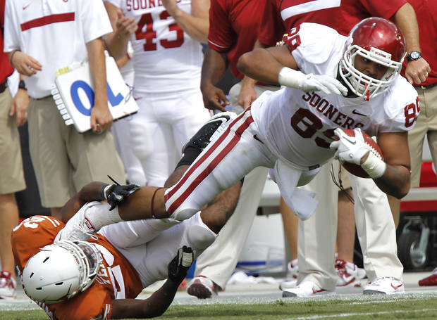 Oklahoma's Austin Haywood (89) is brought down by Texas' Carrington Byndom (23) during the Red River Rivalry college football game between the University of Oklahoma Sooners (OU) and the University of Texas Longhorns (UT) at the Cotton Bowl in Dallas, Saturday, Oct. 8, 2011. Photo by Chris Landsberger, The Oklahoman  ORG XMIT: KOD