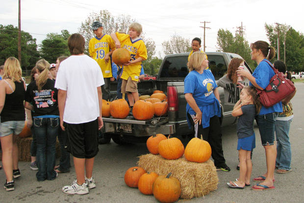 Students sell pumpkins out of the bed of a pickup Thursday during the Choctaw High School Homecoming Festival.