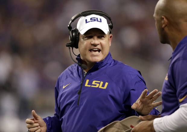 LSU head coach Les Miles, left, talks with his staff on the sidelines in the final seconds of the first half of an NCAA college football game against the TCU, Saturday, Aug. 31, 2013, in Arlington, Texas. (AP Photo/LM Otero) ORG XMIT: TXMO118