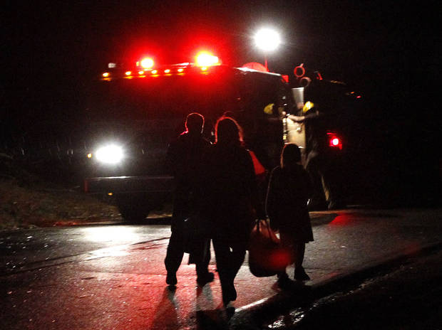 A family walks away from their home carrying a few possessions after a severe storm ripped through the Trussville area in the early hours of Monday, Jan. 23, 2012, in Trussville, Ala.  (AP Photo/Butch Dill) ORG XMIT: ALBD102