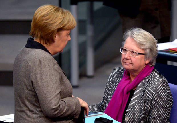 FILE - In this Dec. 13, 2012 file picture German chancellor Angela Merkel, left, talks with education  minister Annette Schavan during a session of the German parliament in Berlin. Germany's education minister has resigned Saturday Feb. 9, 2013, after a university decided to withdraw her doctorate, finding that she plagiarized parts of her thesis - an embarrassment for Chancellor Angela Merkel's government months before national elections.  (AP Photo/dpa, Rainer Jensen,File)