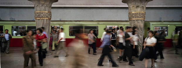 In this Sept. 10, 2012 photo, North Korean commuters move in and out of a train on a subway platform at the metro station in Pyongyang. (AP Photo/David Guttenfelder)