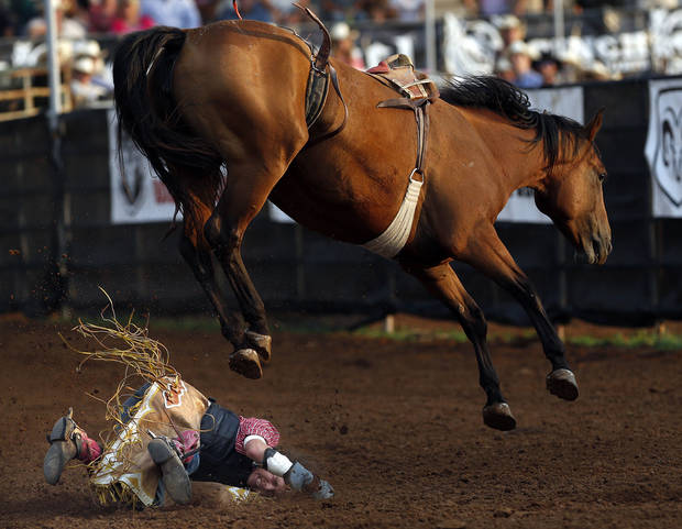 Levi Molesworth is thrown to the ground during the Bareback Bronc at the International Finals Youth Rodeo in Shawnee, Okla., Friday, July 13, 2012. Photo by Sarah Phipps, The Oklahoman
