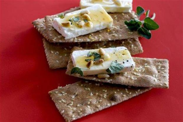 In this undated image, feta cheese and honey are shown served on crackers in Concord, N.H. (AP Photo/Matthew Mead)