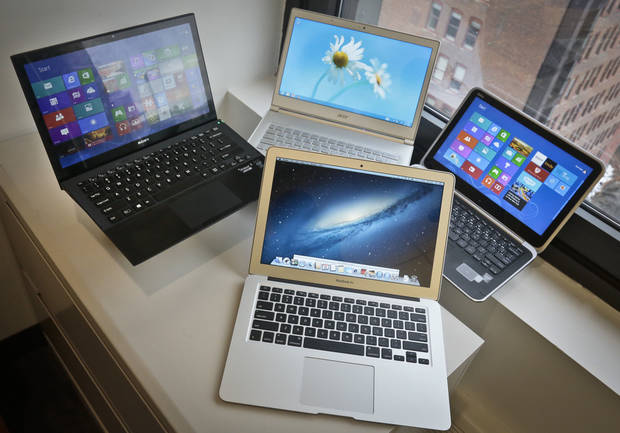 A MacBook Air from Apple, bottom center, a Vaio Pro 13 from Sony, top left, an Aspire S7 from Acer, center, and an XPS 12 from Dell, right, are displayed for a photograph, Thursday, Aug. 22, 2013, in New York. Each notebooks has a microprocessors that belongs to a new family of Intel chips called Haswell.  (AP Photo/Bebeto Matthews)