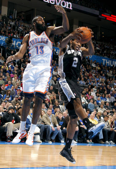 San Antonio Spurs' Kawhi Leonard (2) grabs a rebound in front of Oklahoma City Thunder's James Harden (13) during the the NBA basketball game between the Oklahoma City Thunder and the San Antonio Spurs at the Chesapeake Energy Arena in Oklahoma City, Sunday, Jan. 8, 2012. Photo by Sarah Phipps, The Oklahoman