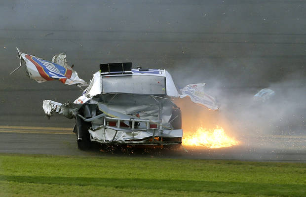 Pieces of Kyle Larson's car fly through the air as he slides down the front stretch after he was involved in a multi-car crash on the final lap of the NASCAR Nationwide Series auto race at Daytona International Speedway, Saturday, Feb. 23, 2013, in Daytona Beach, Fla. (AP Photo/John Raoux)