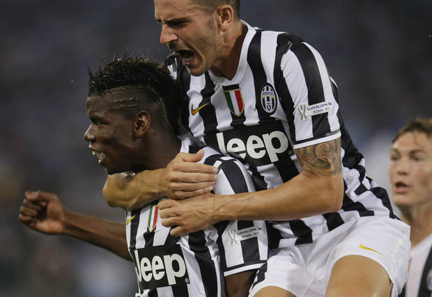 Juventus' Paul Pogba, of France, left, celebrates with teammates after scoring during the Italian Supercup soccer match against Lazio at the Rome Olympic stadium Sunday, Aug. 18, 2013. (AP Photo/Gregorio Borgia)