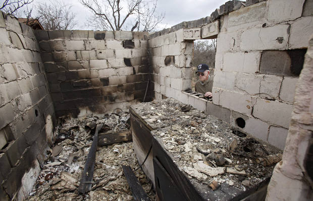 Tex Cyr looks through the window of his destoyed home as he surveys the damage caused by wildfires on Friday, April 10, 2009, in Choctaw, Okla.  Photo by Chris Landsberger, The Oklahoman