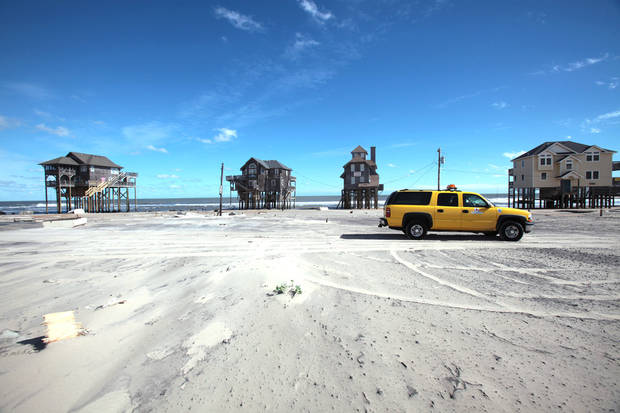 A North Carolina Department of Transportation vehicle drives past beach houses down sand-covered NC 12 in the Mirlo Beach section of Rodanthe, N.C. on Tuesday, Oct. 30, 2012. Located between the first and second houses to the left was, until Hurricane Sandy passed by, a third house which was knocked into the ocean by the storm. People on North Carolina's Outer Banks are facing some flooding and damage from Hurricane Sandy, but emergency management officials say it could have been worse. (AP Photo/The Virginian-Pilot, Steve Earley) ORG XMIT: VANOV307