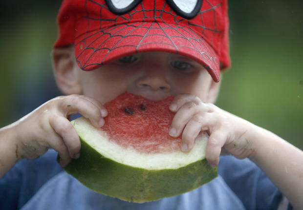 Xander Wilson, 3, eats watermelon during the LibertyFest's ParkFest at the University of Central Oklahoma, Sunday, July 4, 2010, in Edmond, Okla. Photo by Sarah Phipps, The Oklahoman