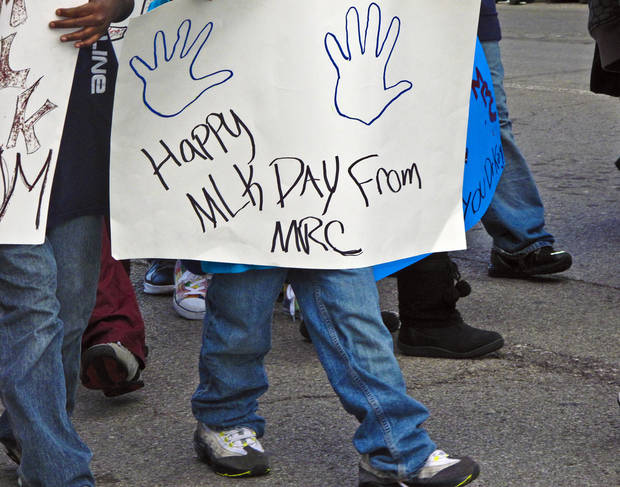 A parade participant carries a sign while walking during Martin Luther King Jr. Day parade through downtown Oklahoma City on Monday, Jan. 16, 2012, in Oklahoma City, Okla. Photo by Tabius Landsberger, The Oklahoman