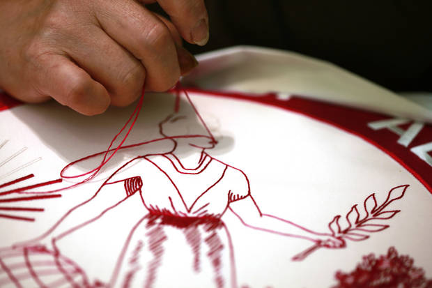   In this Tuesday, June 12, 2012 photo, Hue Duong, 55, hand-embroiders a University of Alabama flag at the Defense Logistics Agency in Philadelphia. In addition to the university banner the military supply operation are the sole producer of the hand-stitched presidential flags. (AP Photo/Brynn Anderson)  