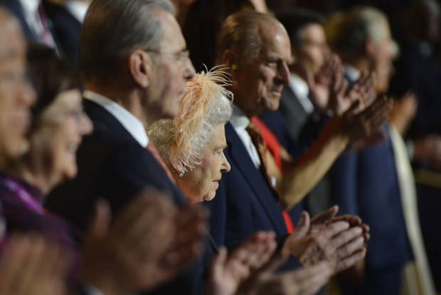 Britain's Queen Elizabeth II, center, is flanked by Britain's Prince Philip, the Duke of Edinburgh, and IOC President Jacques Rogge, left, as she attends the Opening Ceremony of the 2012 Olympic Summer Games at the Olympic Stadium in London, Friday, July 27, 2012. (AP Photo/Toby Melville, Pool)