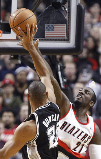 Portland Trail Blazers center J.J. Hickson, right, stretches to block a shot by San Antonio Spurs forward Tim Duncan during the first quarter of an NBA basketball game in Portland, Ore., Thursday, Dec. 13, 2012. (AP Photo/Don Ryan)