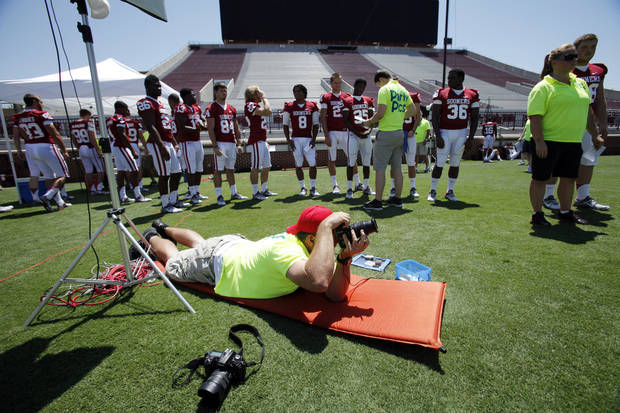 Photographer Brian Allen makes pictures as the team lines up during photo day for the Sooners at Gaylord Family/Oklahoma Memorial Stadium at the University of Oklahoma on Saturday, Aug. 4, 2012, in Norman, Okla.  Photo by Steve Sisney, The Oklahoman