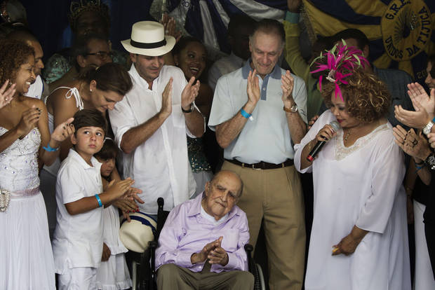 FILE - In this Feb. 12, 2012 file photo, Brazilian architect Oscar Niemeyer, 104, bottom center, Rio de Janeiro's Mayor Eduardo Paes, center left, and Brazil Olympic Committee President Carlos Arthur Nuzman, center right, applaud during the Sambadrome opening ceremony after being reformed in Rio de Janeiro, Brazil.  The Sambadrome parade grounds, that hosts Brazil's Carnival celebrations, was designed by Niemeyer. According to a hospital spokeswoman on Wednesday, Dec. 5, 2012, famed Brazilian architect Oscar Niemeyer has died at age 104.  (AP Photo/Felipe Dana, File)