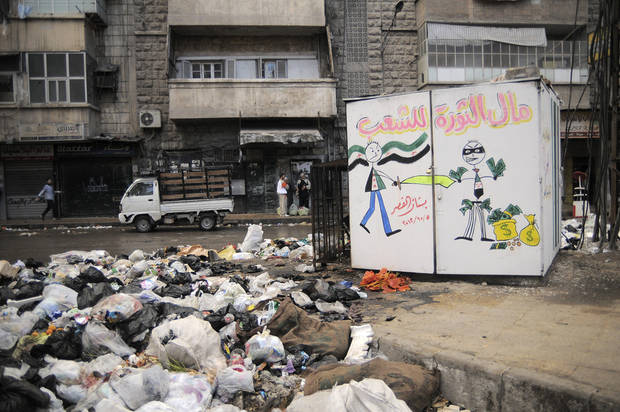 "In this Saturday, Nov. 10, 2012 photo, garbage is plied up in the Al-Buhouth area of Aleppo, Syria. The Arabic writing on the kiosk at right reads, ""the money of the revolution is for the people.""(AP Photo/Mónica G. Prieto)"