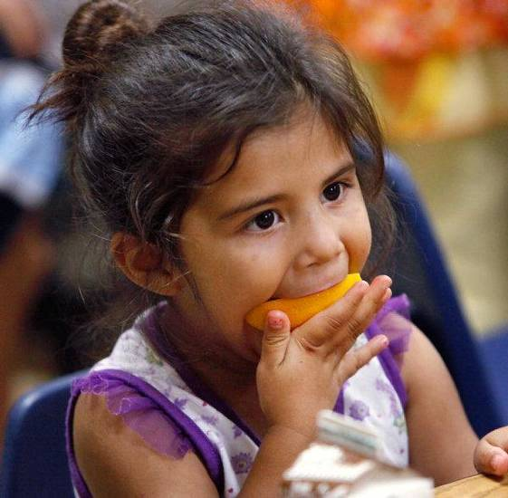 Sophia Cervantes, 4,  chews on an orange during an afternoon meal.  She is among dozens of children who are receiving healthy snacks and meals through a summer feeding program for children.  Novo Ministries partners with the Regional Food Bank Of Oklahoma to feed the children during the summer months while they are out of school. These children are at the Ambassador Courts Community Center.  <strong>JIM BECKEL - THE OKLAHOMAN</strong>