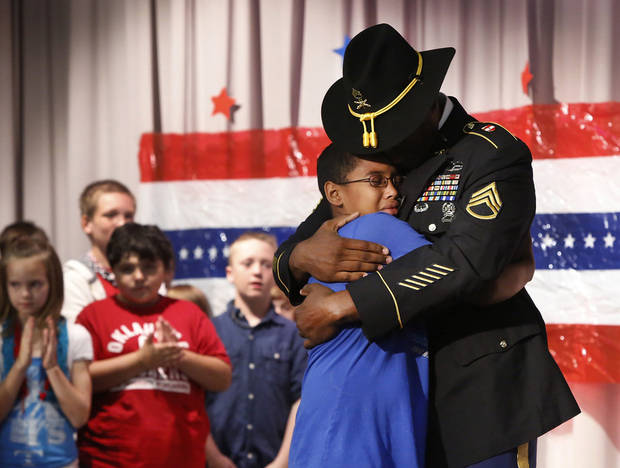 Staff Sergeant Harold Williams surprised his son, Adrian, a fifth grade student during a patriotic-themed Veteran's Day assembly Friday morning, Nov. 9, 2012, at Schwartz Elementary School, when he walked onto the stage while his son and classmates were reciting the preamble of the U.S. Constitution.  The elder Williams arrived at the school this morning and had been hidden off stage until his son's class gathered on the stage. Father and son embraced for nearly two minutes in front of a large red, white and blue backdrop. Adrian wiped away tears and tears also rolled down the cheeks of Sgt. Williams.  Harold has been stationed in Germany with the U.S. Army and recently returned there from duty in Iraq.      Photo by Jim Beckel, The Oklahoman