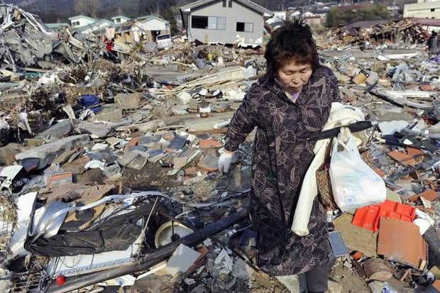 A woman searches through the rubble of her home destroyed in Friday's powerful earthquake-triggered tsunami in Ofunato, Iwate prefecture, northern Japan, Sunday, March 13, 2011. (AP Photo/Kyodo News) JAPAN OUT, MANDATORY CREDIT, NO SALES IN CHINA, HONG  KONG, JAPAN, SOUTH KOREA AND FRANCE ORG XMIT: TTX815