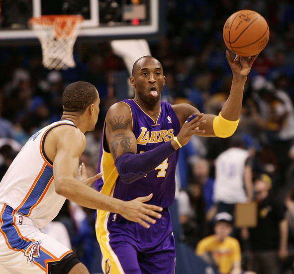 Los Angeles Lakers guard Kobe Bryant passes the ball around Oklahoma City Thunder guard Thabo Sefolosha, of Switzerland, during the first half of an NBA basketball game Sunday, Feb. 27, 2011, in Oklahoma City. (AP Photo/James Schammerhorn) ORG XMIT: OKJS102