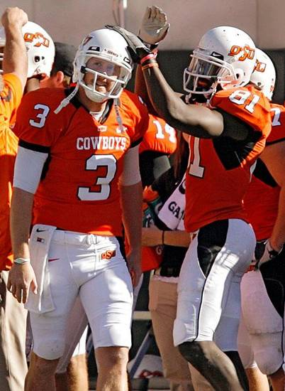 Oklahoma State's Justin Blackmon (81) celebrates with Brandon Weeden (3) as he comes off the field late in the fourth quarter during the college football game between the Oklahoma State University Cowboys and the Baylor University Bears at Boone Pickens Stadium in Stillwater, Okla., Saturday, Nov. 6, 2010. Weeden set an OSU single game passing record. Photo by Chris Landsberger, The Oklahoman