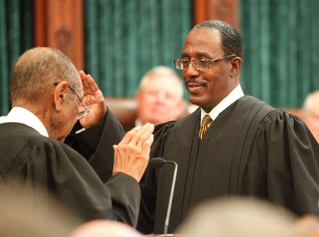 Tom Colbert takes the oath of office as as the first black chief justice of the Oklahoma Supreme Court, Friday, January 4, 2013.  Judge Charles Owens, with his back to the camera, did the swearing in. Photo By David McDaniel, The Oklahoman