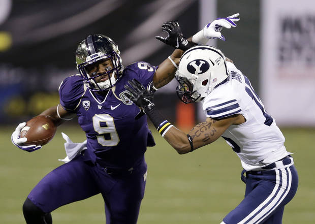 Washington's Damore'ea Stringfellow, left, tries to shake off the tackle attempt from BYU defensive back Michael Davis during the Fight Hunger Bowl last December in San Francisco. (AP Photo/Marcio Jose Sanchez)