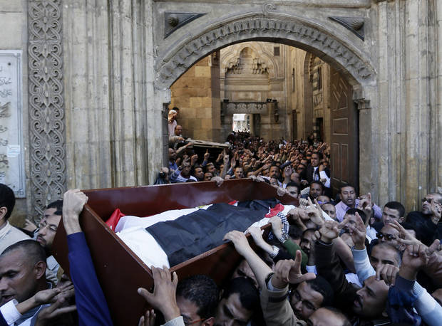 "Muslim Brotherhood and Egyptian President Morsi supporters carry a body of one of six victims who were killed during Wednesday's clashes during their funeral outside Al Azhar mosque, the highest Islamic Sunni institution, Friday, Dec. 7, 2012. During the funeral, thousands Islamist mourners chanted, ""with blood and soul, we redeem Islam,"" pumping their fists in the air. ""Egypt is Islamic, it will not be secular, it will not be liberal,"" they chanted as they walked in a funeral procession that filled streets around Al-Azhar mosque. Thousands of Egyptians took to the streets after Friday midday prayers in rival rallies and marches across Cairo, as the standoff deepened over what opponents call the Islamist president's power grab, raising the specter of more violence. (AP Photo/Hassan Ammar)"